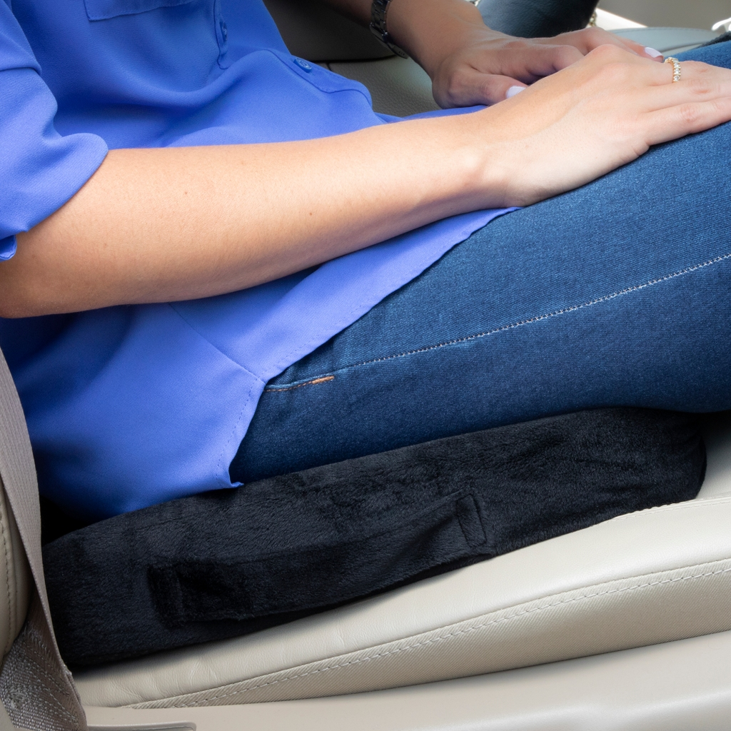 image of a 100% memory foam seat cushion placed on top pf the car seat with the driver of the car seating on top of the cushion
