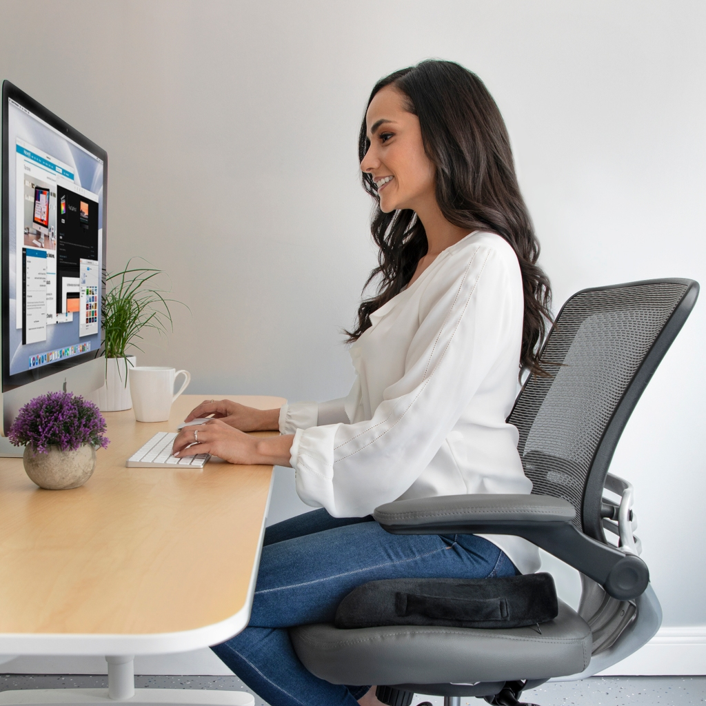 image of a person seating on top of the memory foam seat cushion on an office chair in front of the computer